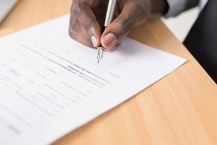 Closeup of someone's hand as they sign a document.