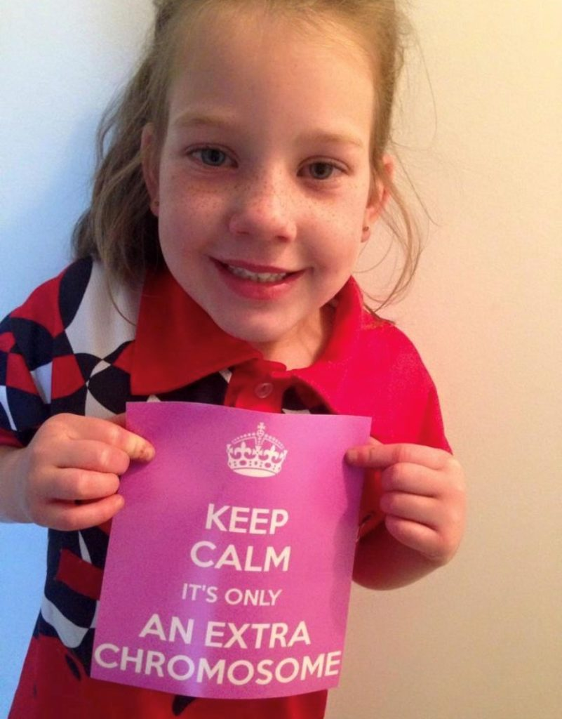 Close up of a young girl holding a pink sign which reads 'Keep calm: it's only an extra chromosome.'