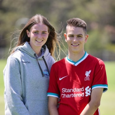 A woman wearing a grey hoodie stands outside next to a teenage boy wearing a red soccer top