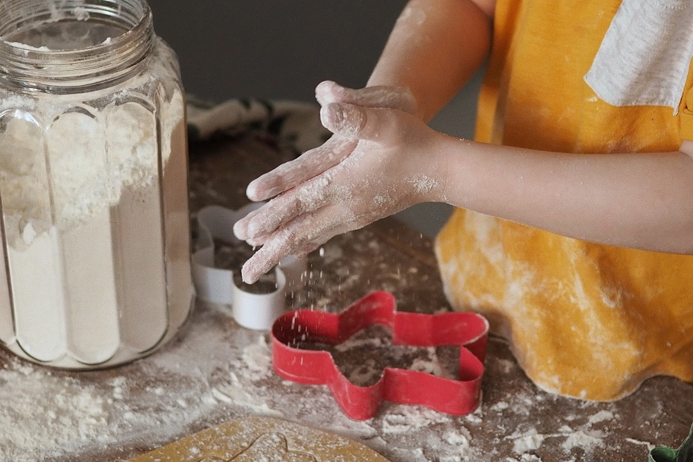 A close-up of a child with flour and gingerbread men-shaped cookie-cutters
