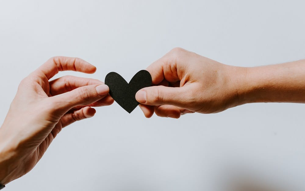 A close up shot of two people holding a cut-out heart